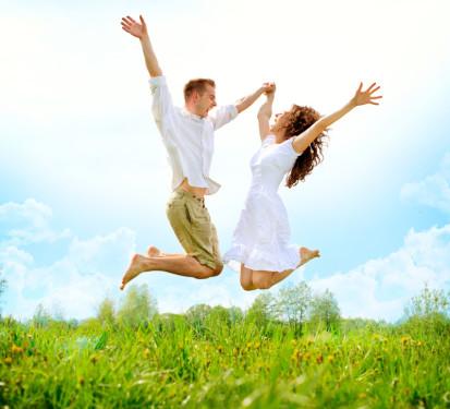 happy couple husband wife celebrating success jumping for joy